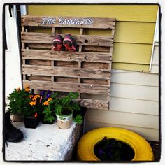 Pallet with our last name and a spray painted tire for a flower pot.  Thank you Pinterest!