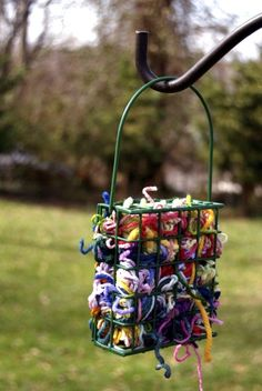 Fill a suet feeder with pieces of yarn for the birds to use to build their nests.  Cute idea. Even if the birds don't take the yarn, it would be a colorful addition to the garden.