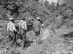 Mountain people carrying a coffin up the creek bed to the family graveyard where it will be buried. Up South Fork of the Kentucky River, 194...