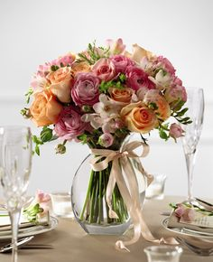 The FTD® Peach Silk™ Arrangement creates a sweet centerpiece to accent your tables on your wedding day. Peach roses, pink freesia, pink ranunculus, pink roses and lush greens are brought together in a classic clear glass vase tied with a peach satin ribbon for an appealing look of grace and charm.