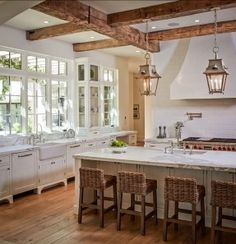 French Country Kitchen with great windows, vintage cabinetry, exposed beams, rustic lanterns, a large island with a sink, and hardwood floors!