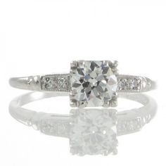 A platinum Art Deco solitaire ring featuring a 0.70ct round transition cut diamond set to four corners with triple split claws raised above a finely railed gallery all to tapering shoulders each set with a pair of single cut diamonds within a millegrain edged surround followed by ribbed detailing that merges to a plain polished band. #RutherfordJewellery #Melbourne
