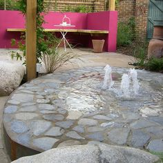 This garden on a new development had to fulfill many functions, entertaining, children's play area, water feature, pergola etc. The resultant garden is a huge success, the hot pink wall helps to contain the eye within the garden, whilst the oak structure ties all the elements together and the water feature is safe for children to play in.