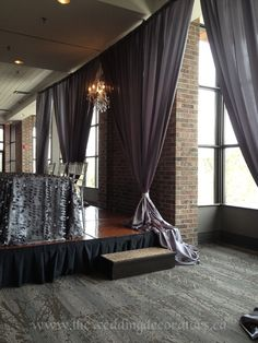 Head table decor feather linens, backdrop draping with chandelier.