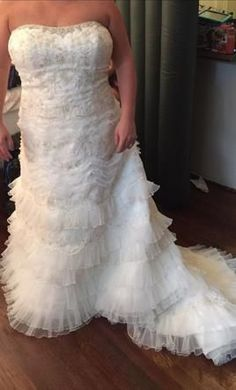 Find ruffled plus size wedding gowns at Darius Cordell Fashion Ltd. This strapless bridal gown design has a heavily beaded bodice.  The a-line cut skirt has tiered ruffles for volume.  As USA custom dress makers we can recreate this lovely #fashion piece with any changes you need. (We also offer affordable replicas of couture #bridalgowns for the bride on a budget.)  See other plus size wedding dresses and get pricing on any picture at www.dariuscordell.com