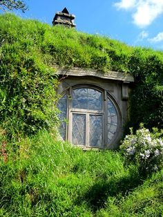 Hobbit window, earth sheltered, chimney, living roof, wall, flowers.