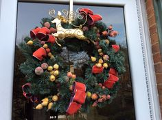 Gold deer, sugared fruit, burgundy ribbon with blue spruce wreaths and garlands are my unifying theme for the front of my home. This is my front door wreath. I was thrilled to find the golden deer wreath holder.