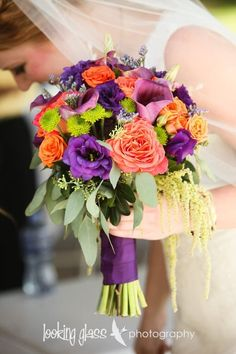 colorful bridal bouquet by linnaea floral design sunset orange roses, purple lisianthus, green hanging amaranthus, seeded eucalyptus, green button mums, purple calla lily, orange roses wedding flowers