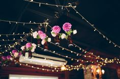PInk flowers hanging over wedding reception tables.
