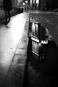 stunning street photography | reflection | puddle | wonderful composition | sidewalk | gutter | reflect | city lights | nightfall | black & white photography