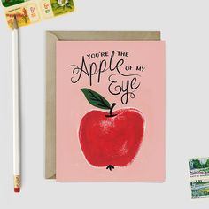 A unique card illustrated with a hand painted apple and the message Youre the Apple of My Eye!. Comes with a pastel green rectangle flap