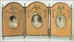 A SILVER-GILT MOUNTED WOOD TRIPTYCH PHOTOGRAPH FRAME BY FABERGÉ, WORKMASTER ANDERS (ANTTI) NEVALAINEN, ST. PETERSBURG, 1899-1904. Each arched-rectangular panel centering a circular aperture, enclosing photographs of Grand Duke George Mikhailovich, Grand Duchess Marie Georgievna, and Princess Nina Georgievna, within a beaded silver border with tied ribbon crest, joined by hinges with pine cone finials, on toupie feet.