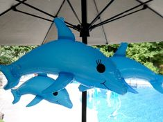 "Pool party ideas for decorations using Inflatable dolphins. Have them ""float"" around the top of the patio umbrellas. Tie them to the umbrella ribs with clear string."