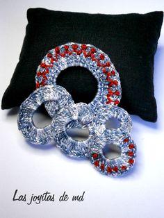 Broche realizado con cinco aros de croché utilizando hilo matizado, cosidos a mano unos a otros formando una unidad y bordado en color rojo.
