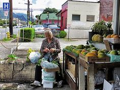 A Chinese woman sorts produce outside her sister's quiet store on Liliha St in Honolulu. The produce store has been open for 28 years, yet the threat of teardown is imminent as new chain businesses are introduced to the area.