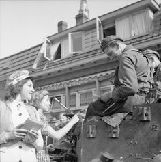 British troops signing autographs for Dutch girls during the liberation of Eindhoven, 19 September 1944.