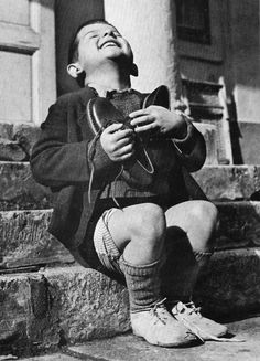 A 6-year-old orphan from Austria ecstatically embraces a brand-new pair of shoes just given to him by the Red Cross, 1946, Gerald Waller