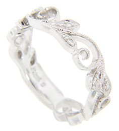 A flowing, vine-like design wraps around this 14K white gold antique style wedding band. The leaves are studded with diamonds. There are approximately .10 carats total weight of diamonds in the ring. It is an elegant ring with a timeless appeal and can be worn with bracketing slim bands. The ring measures slightly over 5mm in width. Also in yellow gold (WB834) and red gold (WB1220). Size: 6 1/2. We can re-size.