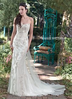 Colleen wedding dress by Maggie Sottero | Luxurious Palatzo satin, sparkling Swarovski crystal embroidered lace, and ethereal tulle combine to create this breathtaking sheath wedding dress, with subtle scoop neckline and pearl button over zipper and inner corset closure. Silk organza Watteau train with beaded lace and Swarovski crystals sold separately.