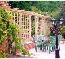 Single Garden Pergola with trellis infill - good for separating area of garden within a traditional garden setting