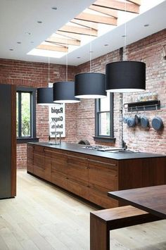 Contemporary Kitchen Design Studio Round Pendant Lamps Wooden Dining Table In The Nearby Countertop Brick Stone Wall.jpeg