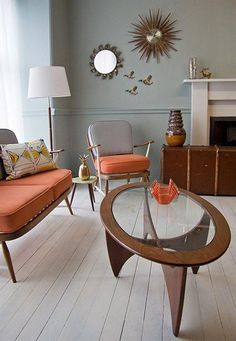 beautiful and stylish mid-cantury coffee table combined with beautiful two seats chair, peach grey arm chair, white floor standing lamp, and fireplace in Swedish home