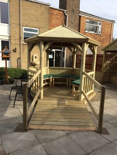 Accessible gazebo with ramp, handrails and seat pads. Part of a care home garden for people with dementia.