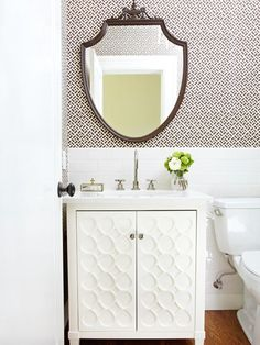 The white brick pattern tile and the neoclassical inspired mirror are the traditional details in this powder room, but the sculptural vanity and geometric wallpaper add a modern design aesthetic.