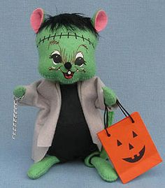 <p> Annalee Doll Description: Green body, black hair, stiches across forehead, black outfit, grey overcoat, holds chain and Trick or Treat bag. Facial expression may vary.</p>