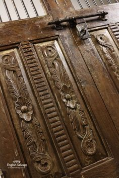 Salvaged double doors, Jali style, including metal bars above two vertical panels, with carved detailing on one side, plus slide bolts and three hinges.