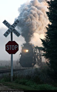 Early morning mist is clearing as #1225 storms across the grade crossing.