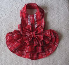 This is made of a soft cotton plaid. There is lace on the bodice and a bow on the back. It fastens at the neck and chest with Velcro and there is a d ring for your leash. Machine Washable.  Size: Small Neck: 8 to 10 Chest: 15 to 18 Length: 13