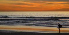 Surfista deixa o mar logo após o pôr do sol em Cardiff, na Califórnia (EUA)