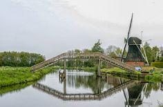 Dutch wooden bridge and windmill by Patricia Hofmeester on Creative Market