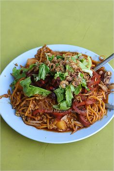 Mee goring mamak is a sweet, spicy and savory dish of yellow noodles stir-fried in a thick mix of black soy sauce with eggs, tomatoes, chili, potatoes, bean curd and vegetable fritters. #noodle #indian #streetfood