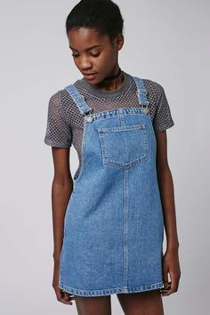 Keep denim looking current in this MOTO pinafore dress. A boxy silhouette cut with a square neckline and deep patch pocket to the front. Team it with a black long sleeve top to finish the look. #Topshop