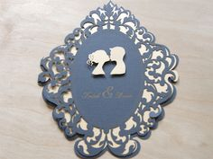 Lovers Cameo laser cut wedding invitations features a couple celebrating their love with a kiss. The elegant floral flourish border is a wonderful design element to frame the couple and add a regal quality to the wedding invitation.