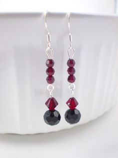 These beautiful dark red and black dangle earrings are made with siam swarovski crystals and black glass beads- perfect for a special occasion and every day use. They will make a terrific gift for one's self or for someone special. These earrings come in a cute organza bag ready for gifting.  LENGTH: 2 inches total (ear wire to end of lowest bead)