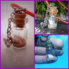 Colgante veraniego, botellita de cristal con arena y una caracola, y con un charm de un cangrejo. Playero total!