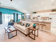 A fully-open living area is perfect for entertaining! Clean white is offset by a vivid blue. Highland Homes' Serendipity model home in Davenport, Florida.   Click to see more photos of this beautiful home.