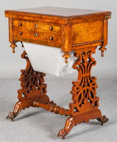 A very good Victorian burr walnut work table.The hinged, cross banded and gadrooned edged top swivels and lifts to reveal a cross banded and baized interior. Below, 2 burr walnut veneered drawers with turned knobs and raised brass escutcheons with the re-covered sliding basket beneath. The canted corners finished with turned finials. Good dual, pierced and carved end supports with turned stretcher and carved cabriole legs with original brass castors