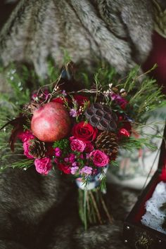 Classic jewel tone shades are made even more fall-appropriate with the addition of pinecones and fruit in this bridal bouquet! Use your bouquet as a chance to incorporate seasonal details and added texture for an unexpectedly gorgeous result.