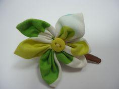 Jolie barrette en coton dans les tons noir, vert, jaune et blanc, en forme de fleur, avec un coeur en bouton jaune. La barrette est une pince crocodile métal de 4.5 cm. Tarifs : 4€ + fdp