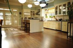 On the walls, the light robin's-egg blue-green color is Saybrook Sage by Benjamin Moore. The cream color of the cabinets is Alexandria Beige by Benjamin Moore.  Two-tiered island, with butcher block from IKEA on one side and a black granite bar with pull-up stools on the other.