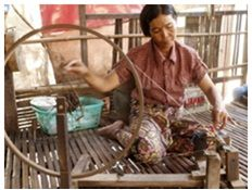 A microcredit client in Cambodia uses the spinning wheel to work on her crafts.
