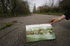 The evacuated city of Pripyat, once brimming with life, is now a chilling ghost town. For an exiled resident, the stillness of a city boulevard stirs memories of her former life. In her hand is an old photo of the same street years earlier. [Pripyat, Ukraine 2005]Gerd Ludwig/INSTITUTE