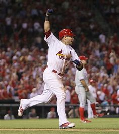 Cardinals' Yadier Molina celebrates as he rounds the bases after tying the game with a two-run home run off of Philadelphia starting pitcher Joe Blanton (background) in the fifth inning during a game between the St. Louis Cardinals and the Philadelphia Phillies on Thursday, May 24, 2012, at Busch Stadium in St. Louis.