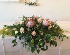 This lovely bridal table floral decor was done by one of the wedding guests using our Kings, fynbos and greens. The addition of roses and lisianthus always gives a soft and romantic feel to any arrangement. We supply fynbos as well as arrange - get in touch for a chat about your next event! Bridal Table, Wedding Bouquets, Floral Wreath, Roses, Romantic, Touch, Wreaths, Table Decorations, Home Decor