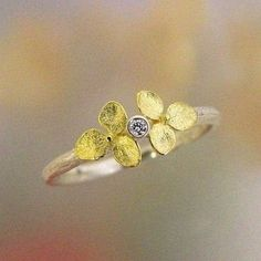 A brilliant-cut (and conflict-free) round diamond is framed by tiny yellow-gold flowers, inspired by hydrangea blossoms, in this lovely ring.