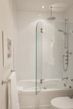 Greg  Rob's Sky Suite House Tour Toronto - white bathroom with glass door that opens for shower in bathtub